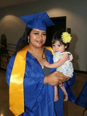 Maria Sanchez holds her 6-month-old daughter Mia before the start of Holloway High School's graduation on Friday May 18 at LifePoint Church in Smyrna.