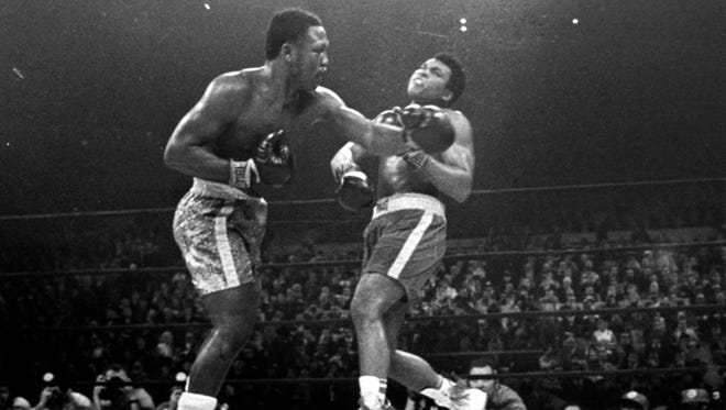 Joe Frazier, left, hits Muhammad Ali during the 15th round of their heavyweight title fight at New York's Madison Square Garden on March 8, 1971.
