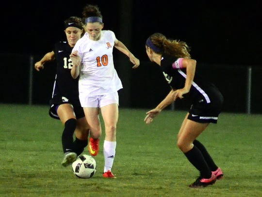 Beech freshman Jana Claire Swafford dribbles between Station Camp sophomore Macy Carter (12) and senior Lauren Smith during second-half action of Tuesday's match.