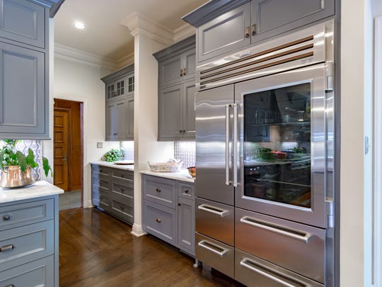 A completely remodeled kitchen showcases marble countertops,