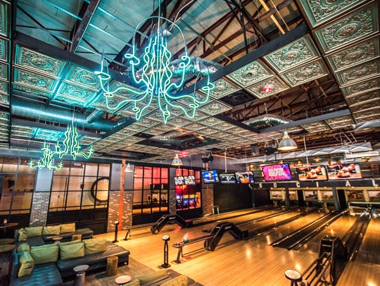 Neon chandeliers hang over bowling lanes at Punch Bowl