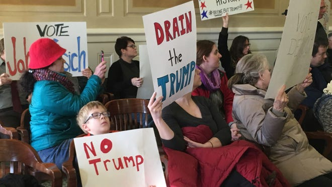 Protesters hold signs in the Arkansas Capitol's old Supreme Court chamber Monday, Dec. 19, 2016, as members of the Electoral College give the state's six votes to President-elect Donald Trump in Little Rock, Ark. Protesters filled the public seating area as the Electoral College members cast their ballots. A brief shouting match broke out following the vote.