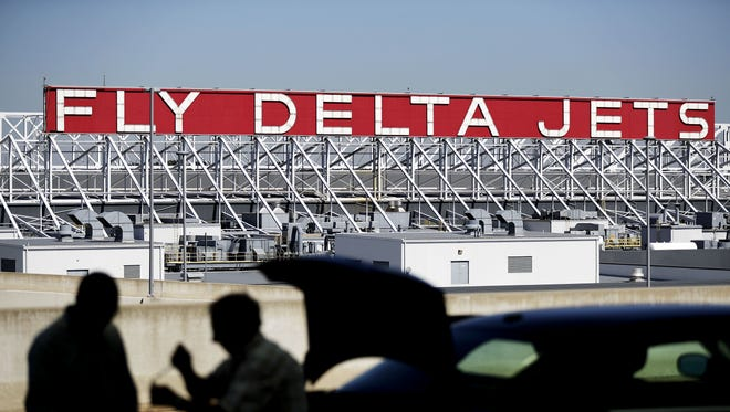 In this Thursday, Oct. 13, 2016, file photo, a Delta Air Lines sign overlooks the unloading area at Hartsfield-Jackson Atlanta International Airport,