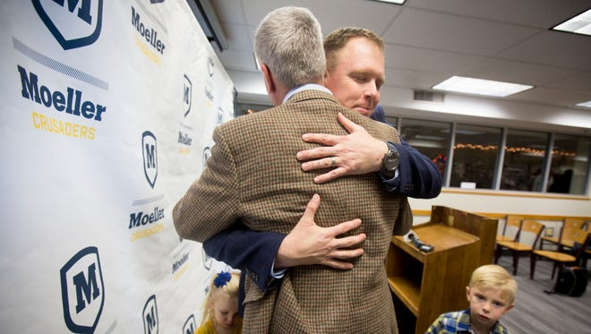 Mon., Dec. 4, 2017: Doug Rosfeld (facing) gets a hug from Charlie Blum, whose sons were coached by Rosfeld during his previous stint at Archbishop Moeller High School. Rosfeld's kids Hope, 2, and Patrick, 4, stand beside him. Rosfeld was named the school's sixth head football coach and returns to the high school ranks after spending three seasons as the Director of Player Development for University of Cincinnati football. Rosfeld was previously a Moeller offensive line coach and teacher before joining UC. He was one of the 1996 football captains of the Crusaders when he attended Moeller.