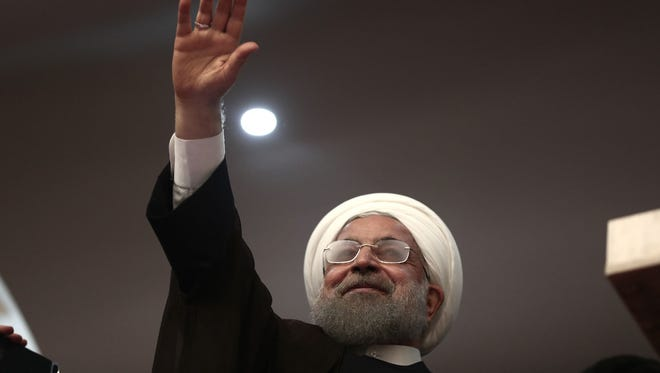 Iranian President Hassan Rouhani waves during a campaign rally in the northwestern city of Ardabil on May 17, 2017.