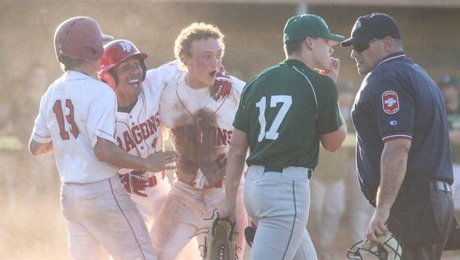 New Palestine players celebrate at home plate after a walk-off win versus Lawrence North in sectional action.