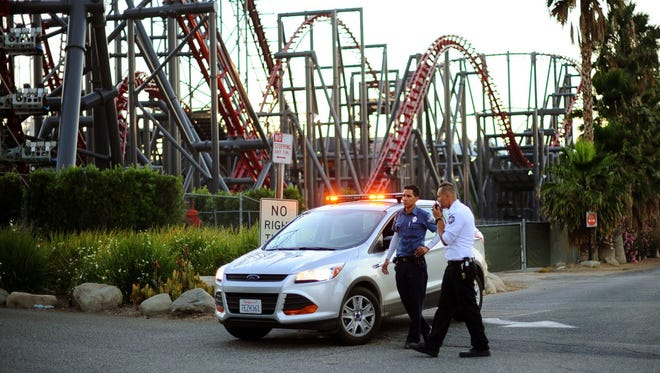 Members of the Six Flags Magic Mountain amusement park security staff monitor the situation at the exit of the park after riders were injured on the Ninja coaster Monday.