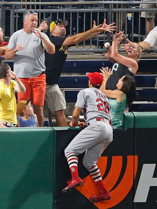 St. Louis Cardinals left fielder Tommy Pham (28) watches as fans bobble the ball on a walk-off, three-run home run by Pittsburgh Pirates' Josh Bell off Seung-Hwan Oh during a baseball game in Pittsburgh, Friday, July 14, 2017. The Pirates won 5-2. (AP Photo/Gene J. Puskar)