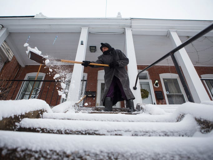 Nellie Sturgis tosses snow of her front steps while