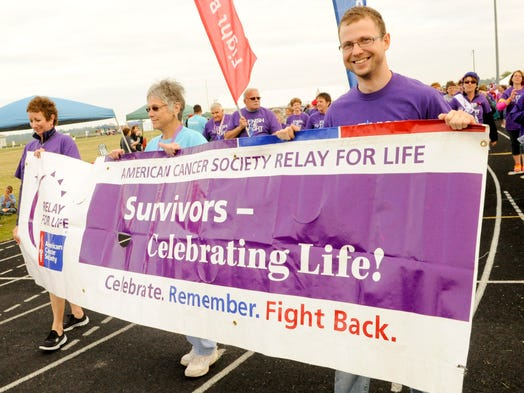 From left, Patsy Walesh, Sharon Wondrash and Zach Thorne carry the relay banner to lead the survivor's lap during the American Cancer Society Relay for Life of Manitowoc County at Two Rivers High School. Sue Pischke/HTR Media. Photo taken on Friday, July 25, 2014.