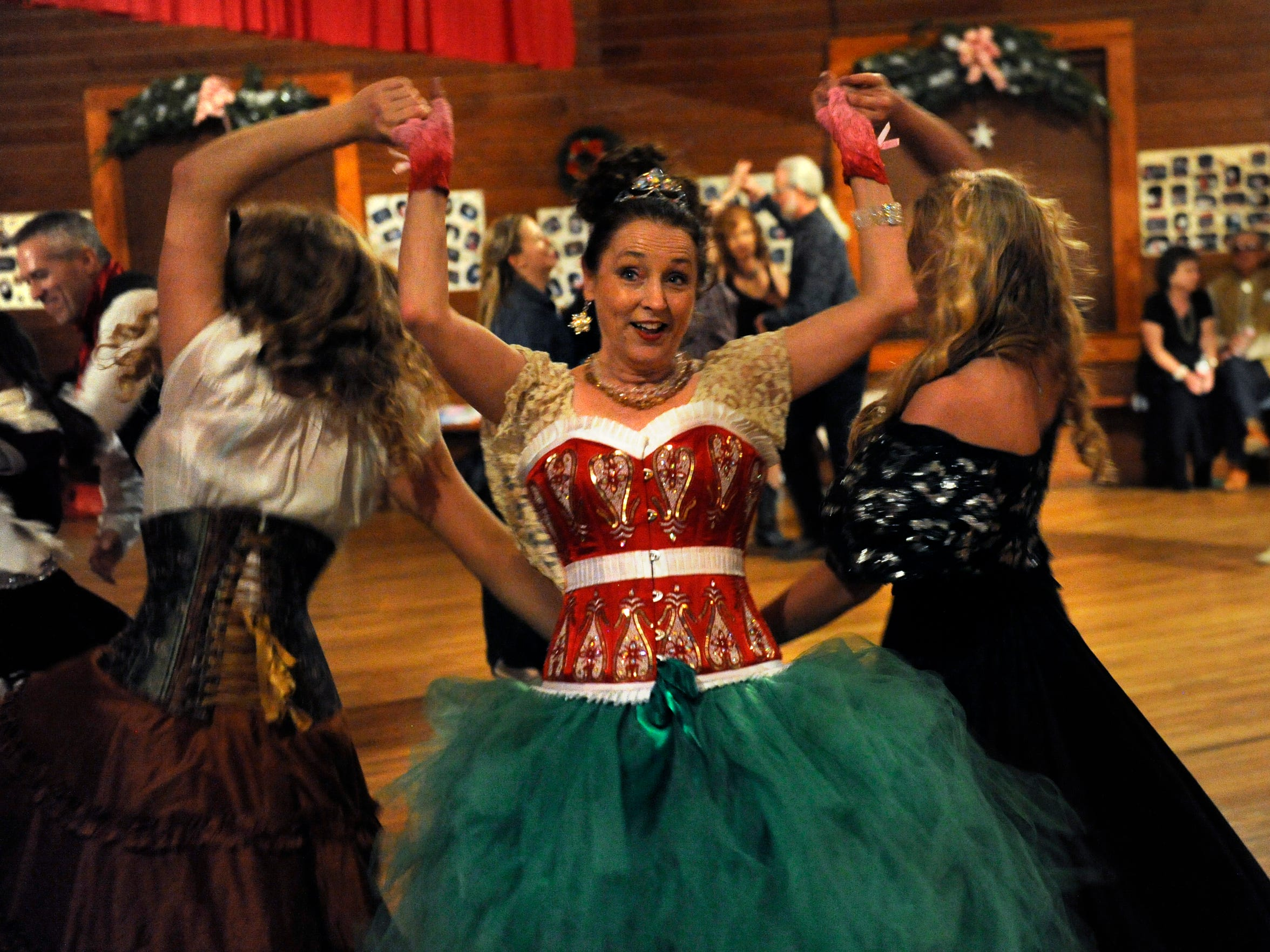 Devon Dawson holds the hands of Kristyn Harris (left) and Mikki Daniel as the three friends dance at the 2015 Texas Cowboys' Christmas Ball. Harris and Dawson performed for the crowd before Michael Martin Murphey's main act at the 130th re-enactment of the dance.