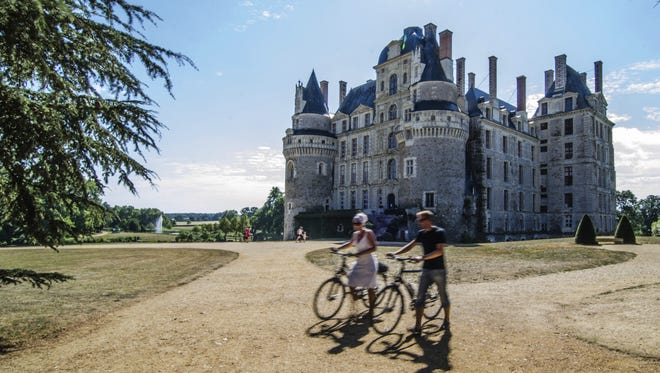 Cyclists make their way past Chateau de Brissac in France's Loire Valley.