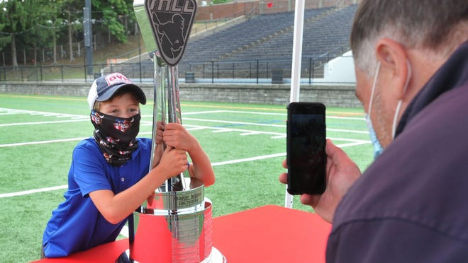 James Lavey of Quincy, right, takes a picture of his son, Brian Lavey, 9, with the Boston Cannons' Major League Lacrosse Championship Trophy during a celebration at Veterans Stadium in Quincy, Thursday, Aug. 27, 2020. Tom Gorman/For The Patriot Ledger