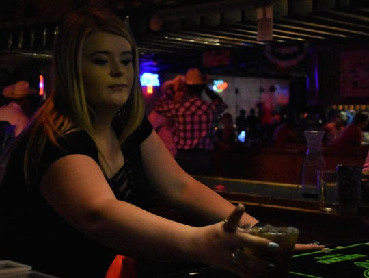 Bartender Hannah Beeson hands a drink to a customer