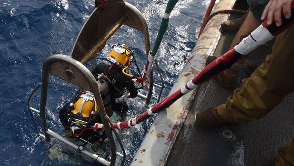 U.S. Navy Divers of Mobile Diving and Salvage Unit 2 prepare to lower the stage to conduct an underwater recovery operation in the Tyrrhenian Sea, Italy, on Oct. 6.