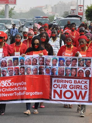 Nigerians walk along Ahmadu Bello Way in protest to bring attention to the one year anniversary of the kidnapping of hundreds of Nigerian school girls in Chibok, Abuja, Nigeria, on April 13, 2015.