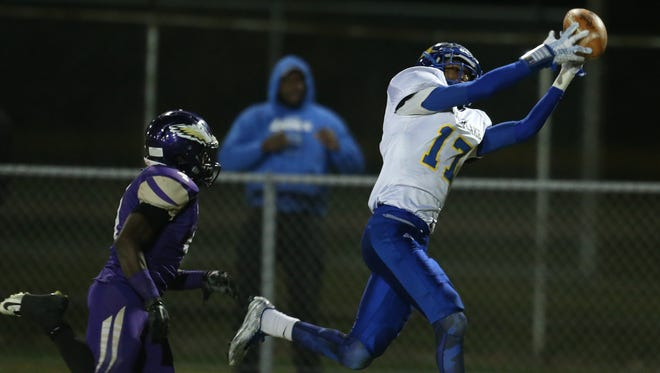 St. Clair Shores South Lake's Jerodd Vines, right, catches a touchdown pass against Madison Heights Madison on Friday, Oct. 16, 2015, in Madison Heights.