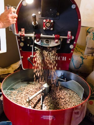 Coffee roaster Bill Palmer releases beans from the roaster at Emy J's in Stevens Point.