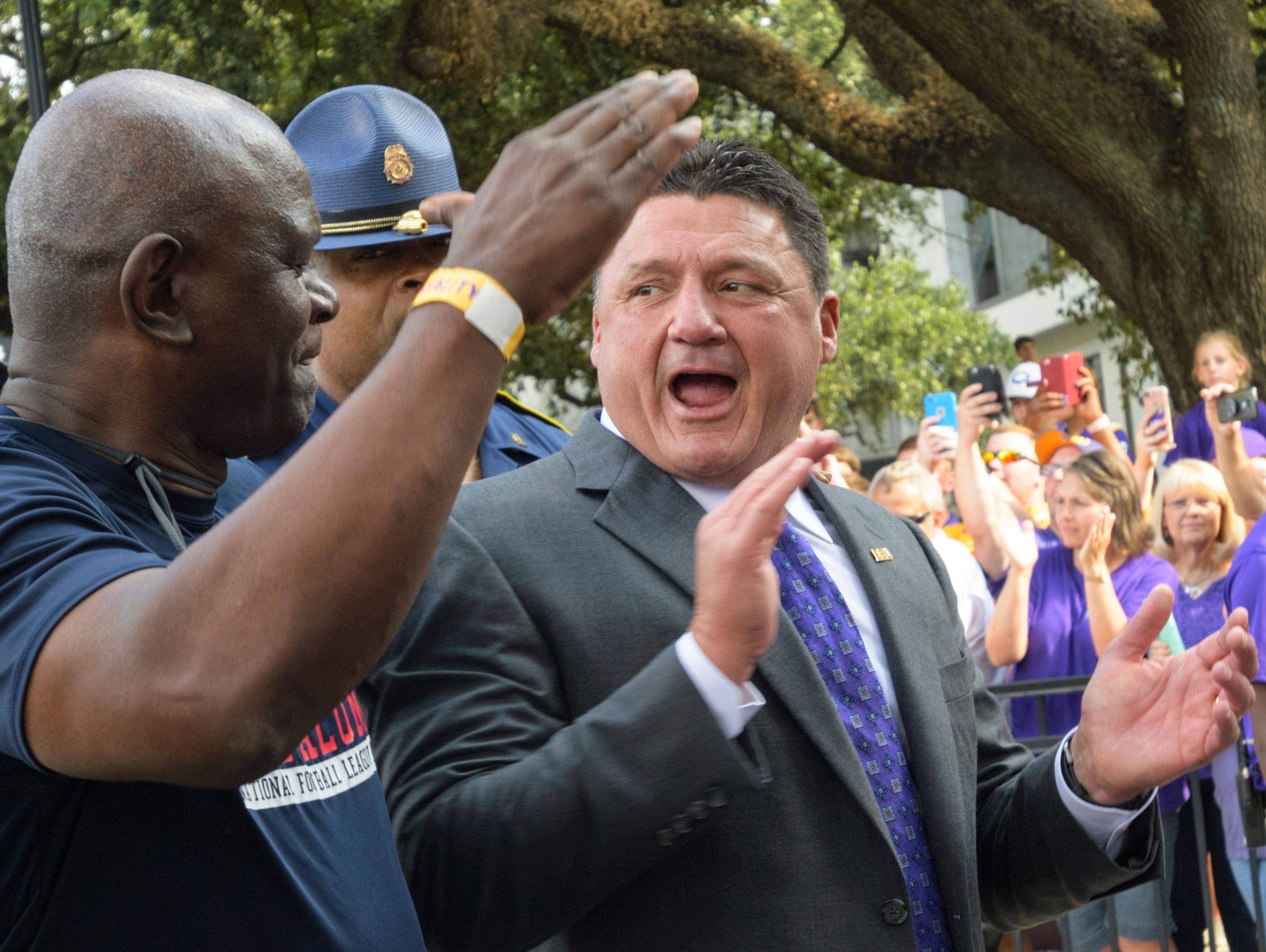 LSU head coach Ed Orgeron, right, greets LSU alumni before an NCAA college football game against Troy in Baton Rouge, La., Wednesday, Sept. 30, 2017.