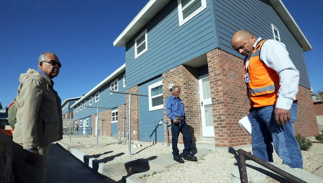 Tony Rivas, right, a construction project manager for the Housing Authority of the City of El Paso, on Monday looks at a rock wall fence with Oscar Carrasco, left, a facility inspector with the agency, during an exterior inspection of a block of apartments at the Woodrow Bean public housing complex at 1313 N. Saint Vrain.