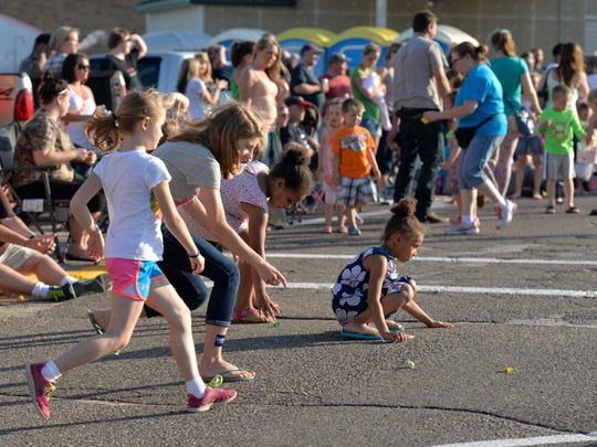 Children scramble after candy along Dewey Street at Foley Fun Days in June 2014.