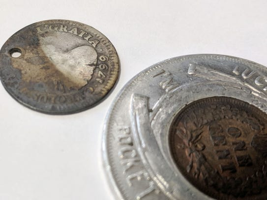 Coins from a 1904 are displayed at a special farewell