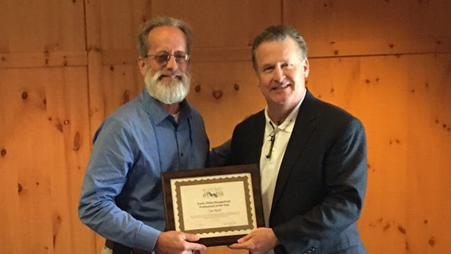 Oakland County Water Resources Commissioner Jim Nash (left) accepts his award from MWEA board member Brian Ross.