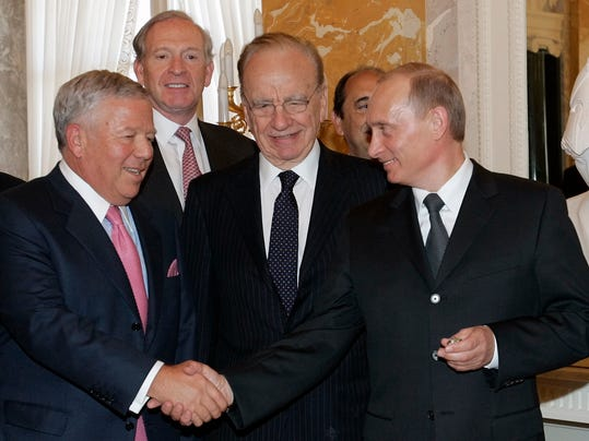 File- This June 25, 2005, file photo shows Russian President Vladimir Putin, right, shaking hands with New England Patriots owner Robert Kraft, left , while holding Kraft's diamond-encrusted 2005 Super Bowl ring, as News Corp. Chairman Rupert Murdoch, center, looks on during a meeting of American business executives at the 18th century Konstantin Palace outside St. Petersburg, Russia. President Donald Trump has a Super Bowl ring  just like Putin. The New England Patriots said Tuesday, Aug. 22, 2017, that owner Robert Kraft gave the diamond-encrusted ring to Trump. The sitting president usually receives gifts from teams during celebratory White House visits. A personalized jersey is standard, but Kraft gave Trump a ring as well.(AP Photo/Alexander Zemlianichenko,file)