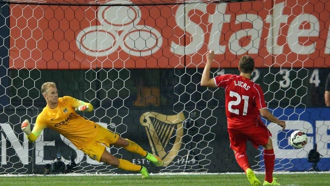 Liverpool FC midfielder Lucas Leiva (21) scores a goal against Manchester City FC goalkeeper Joe Hart during penalty kicks of a game at Yankee Stadium.