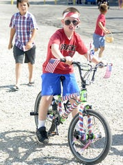 Axle Jones, 9, rides his bike in the kids' parade.
