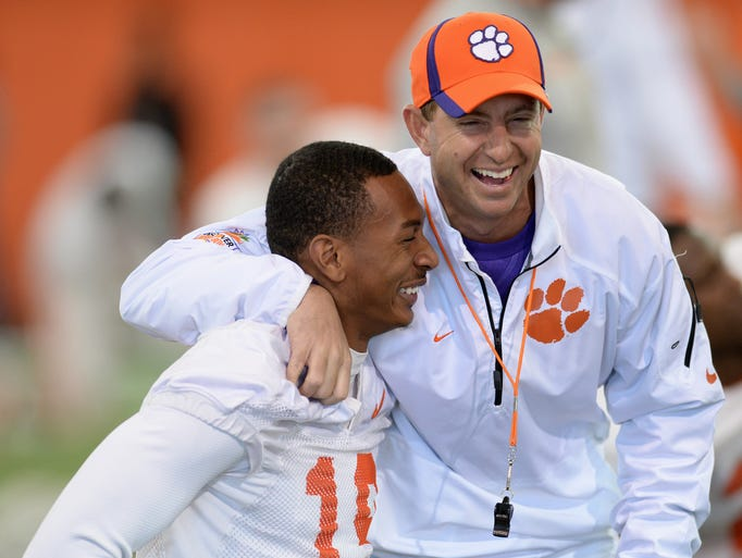 Clemson head coach Dabo Swinney laughs with wide receiver Charone Peake (19) during practice Wednesday, March 26, 2014. BART BOATWRIGHT/Staff