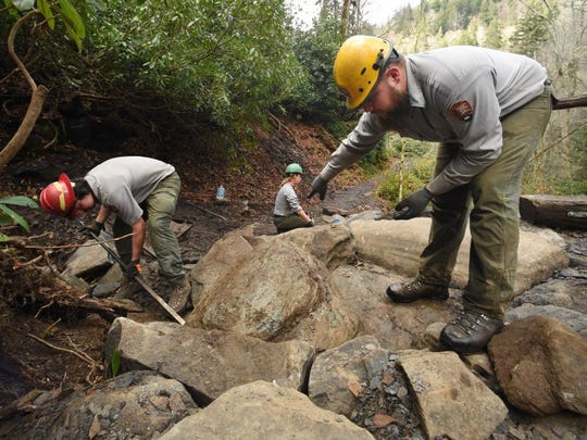 Trails Forever crew members move boulders to stabilize