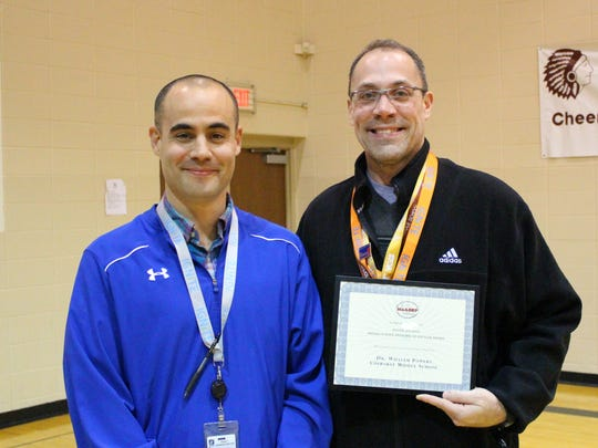 Shane Dublin, who oversees middle and high schools, presents award to Bill Powers, principal of Cherokee Middle School.