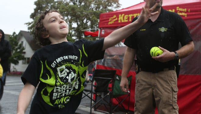 Aiden Larimer, 9, throws a direct hit to sink Stayton Chief of Police Rich Sebens in a dunk tank during the Santiam SummerFest on Saturday, July 25, 2015, in Stayton, Ore.