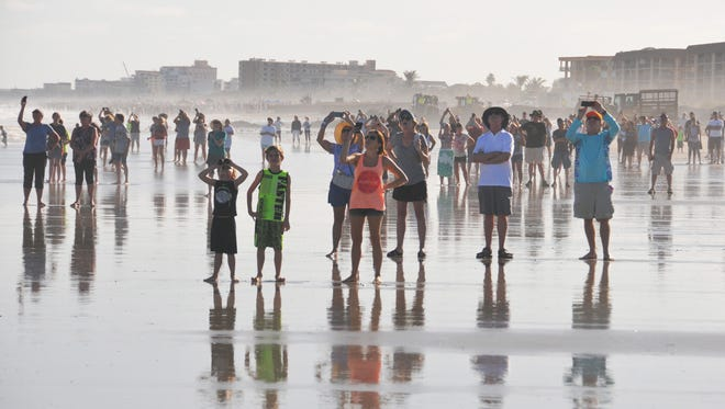 As seen from Cape Canaveral's beach: Crowds watch SpaceX's Falcon Heavy rocket launch from Kennedy Space Center on Tuesday, Feb. 6, 2018.