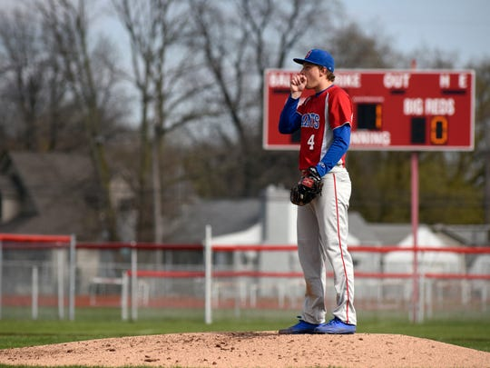 Saints' pitcher Gehrig Anglin warms up his hand before tossing in a pitch Monday, April 17, during boys baseball action at Port Huron High School.