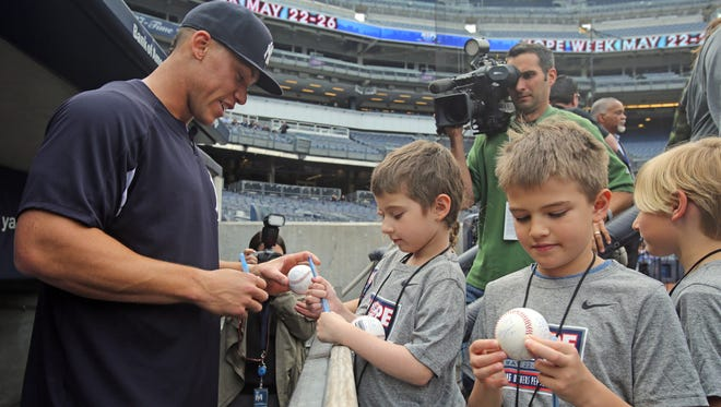 Yankee Aaron Judge signs the balls of Scarlett Chwatko, 6, Max Chwatko, 8, and Alex Travin, 8, before the start of the game at Yankee Stadium in the Bronx May 24, 2017. The kids got the Yankees royal treatment during HOPE WEEK which included lunch with Judge and Brett Gardner, and a tour of the Saturday Night Live studio.