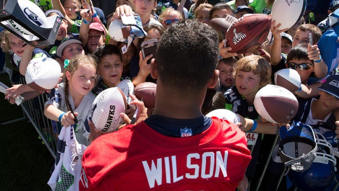 Seattle Seahawks quarterback Russell Wilson signs autographs for young fans during an NFL football training camp on Friday, July 31, 2015, in Renton, Wash.  Russell Wilson is sticking around with the Seattle Seahawks. Wilson tweeted Friday morning that he has agreed to a four-year contract extension with the Seahawks, keeping him with the franchise that took him in the third round of the 2012 draft and watched him become one of the most successful young quarterbacks in NFL history.