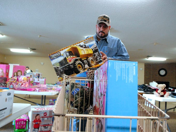 Everardo Rivera looks for presents for his three children at the Eastern Area Community Ministries ÒshopÓ at the Middletown Seventh Day Adventist Church where families that utilize the organizationÕs services year-round can buy Christmas gifts for loved ones.  Dec. 12, 2013