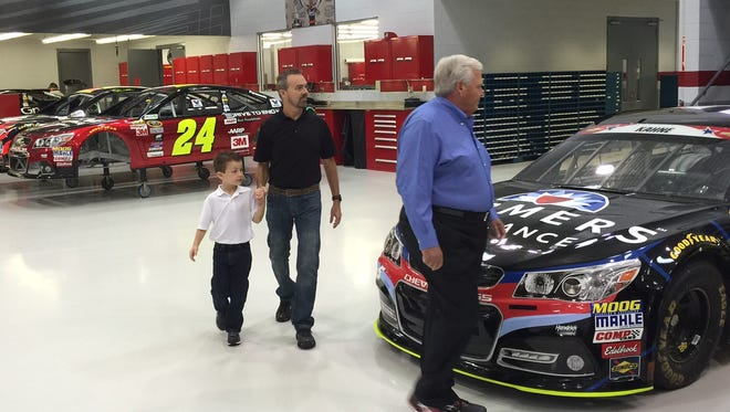NASCAR team owner Rick Hendrick gives Rick Groesbeck and his 6-year-old son Garrett a tour of the Hendrick Motorsports shop.