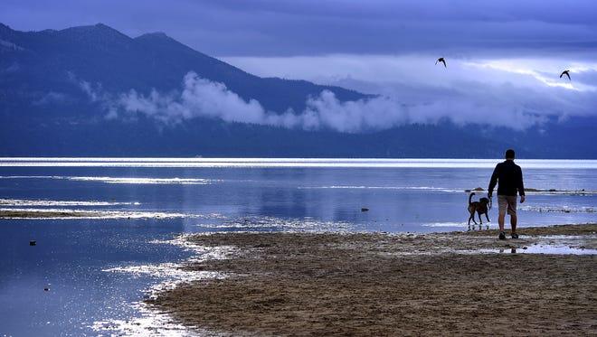 A man and his dog walk on the shore of the lake at South Lake Tahoe.