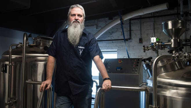 Owner John Mills II poses for a portrait near his brew equipment at Maiden's Brew Pub on Friday, Feb. 2, 2018. Mills got his start as a home brewer before deciding to open his own brew pub.