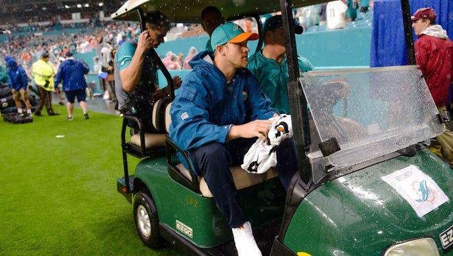 Miami Dolphins quarterback Ryan Tannehill (center) is seen leaving in a golf cart after defeating the Arizona Cardinals at Hard Rock Stadium.
