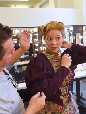 "Actress Melissa Dull looks at herself in the mirror after director Hank Fitzgerald helped her put on the wig for the character Mrs. Winifred Banks in ""Mary Poppins."" The play runs Aug. 6-9 and Aug. 13-16 at ShenanArts. As part of Family Night Out, the cast will be performing at the Sunspots Pavilion stage at 6 p.m. on July 24."