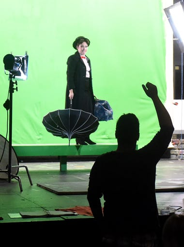 Dressed as Mary Poppins, actress Liz Leone holds her umbrella and bag as she receives instructions from director Hank Fitzgerald who is off stage. They film against a green screen for a commercial on July 8, 2015.