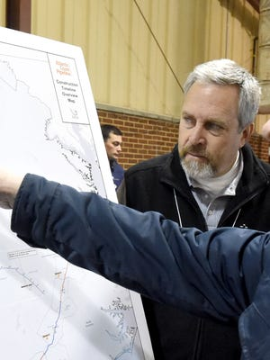 Bryn Smith, an economic development manager with Dominion, listens to a question about the proposed construction timeline while referencing a map during an Atlantic Coast Pipeline construction expo held at Augusta Expo in Fishersville on Thursday, Dec. 8, 2016.