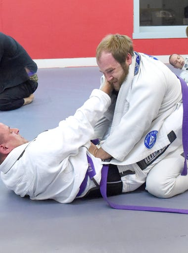 Brian Rose and Scott Allyn, both purple belts in Brazilian jiu-jitsu, live roll (aka. spar) against one another as students pair off to go one-on-one during class at Total Defense Martial Arts in Staunton on Jan. 24, 2017.