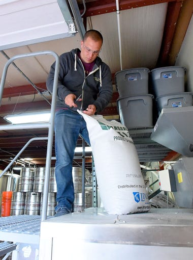 Owner Aaron Allen opens another bag of grain to be ground in preparation for brewing, happening later in the week, at Seven Arrows Brewing Company in Waynesboro on Monday, April 17, 2017.