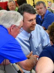 Del. Ben Cline, R-Rockbridge, talks to Del. Dickie Bell, R-Staunton, and others while attending a barbecue and politics event sponsored by the Greater Augusta Regional Chamber of Commerce at Augusta Expo in August 2017.