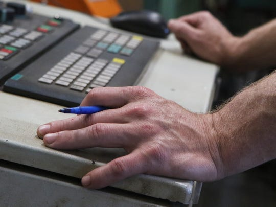 Bailey Hogue operates a Peddi Writer, a computer-controlled machine that automatically marks out measurements on steel beams, at Steel Fabricators of Monroe on Thursday, November 17, 2016.